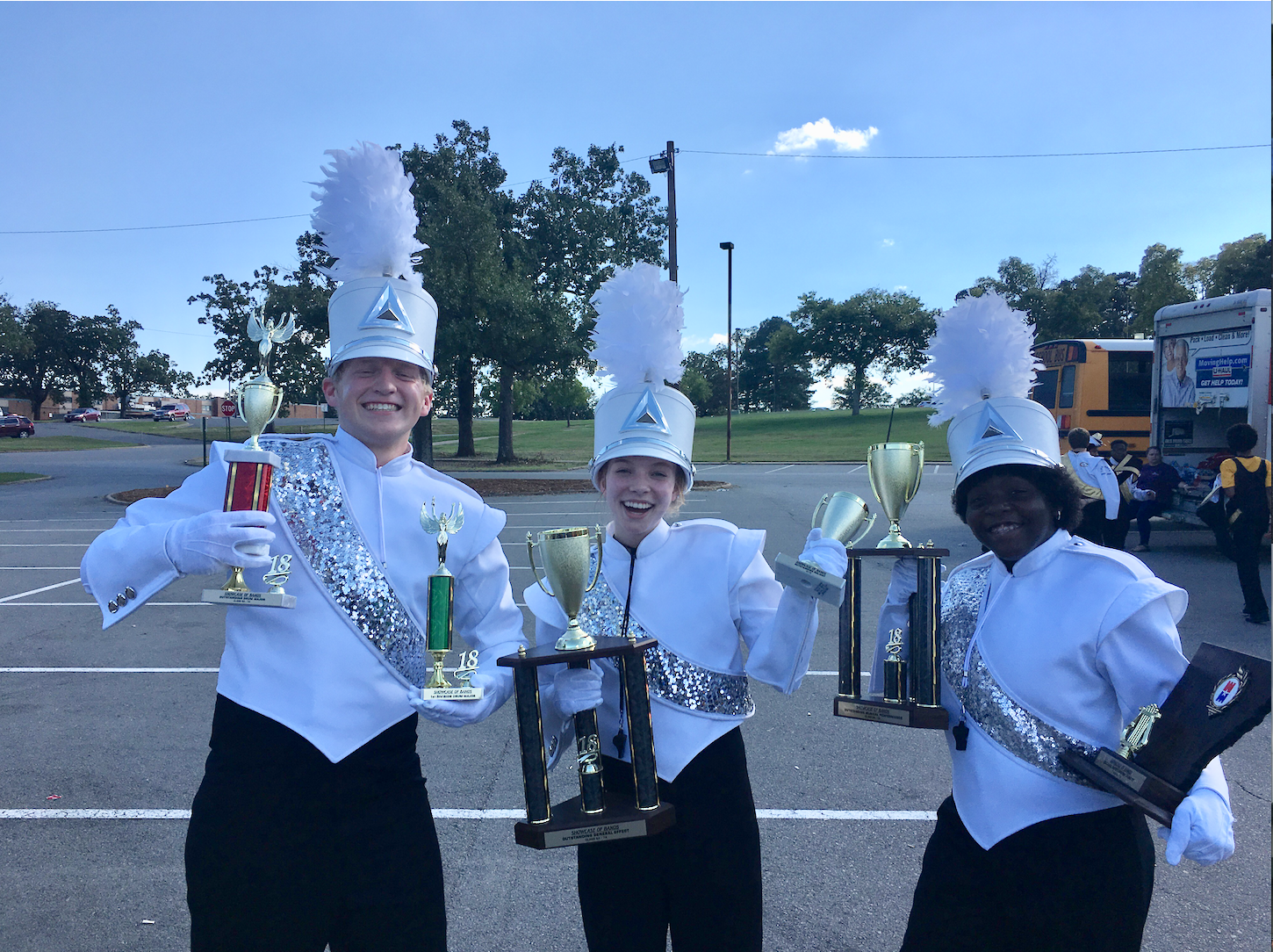 Drum Majors Chris Walters (left), Riley Parker (middle) and Journee Jones (right)show off Conway's numerous trophies earned at War Memorial.