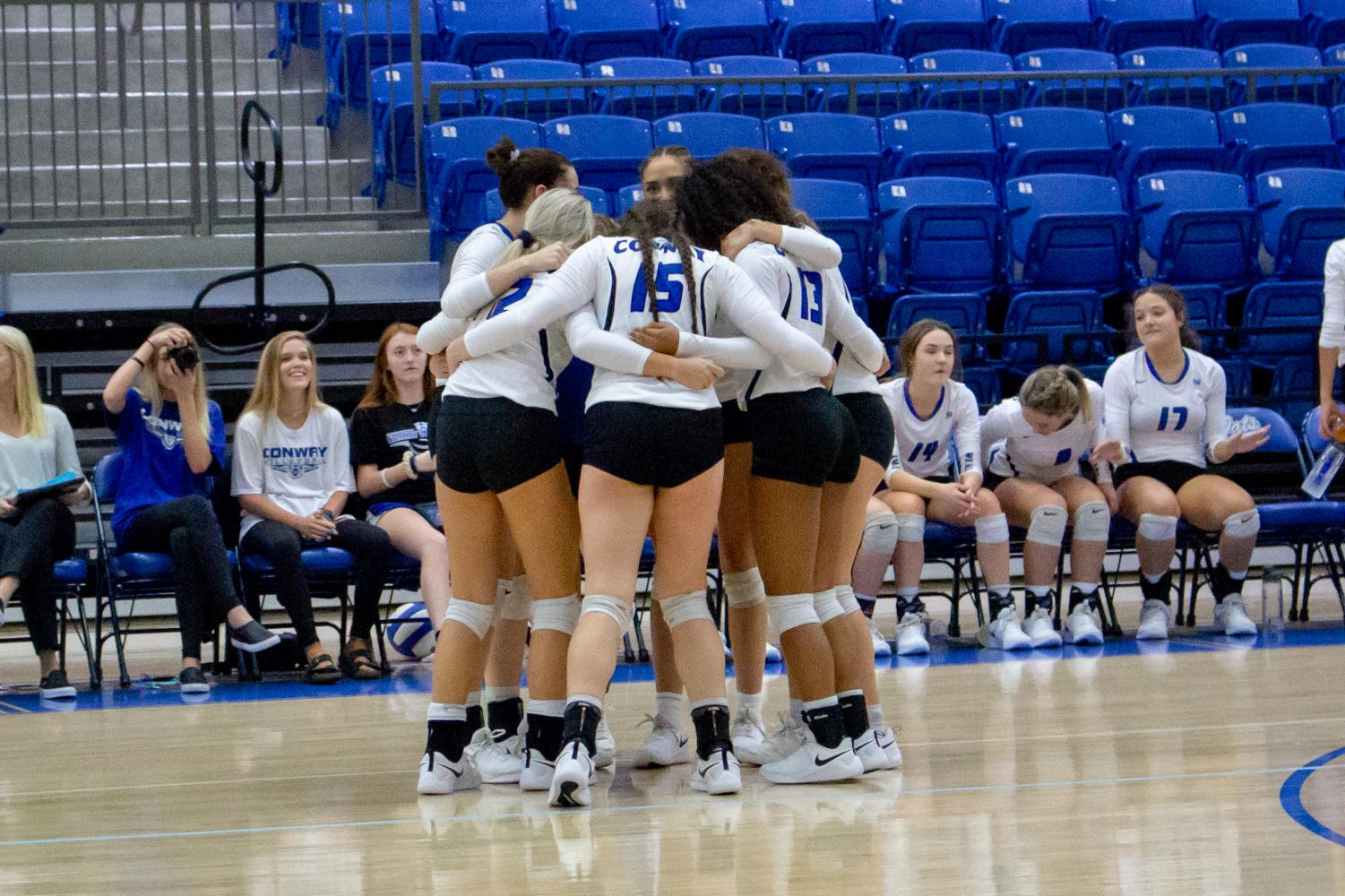 The Lady Cats huddling together before a set
