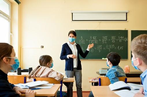 A teacher wearing a N95 Face masks teaches mathematics at an High School